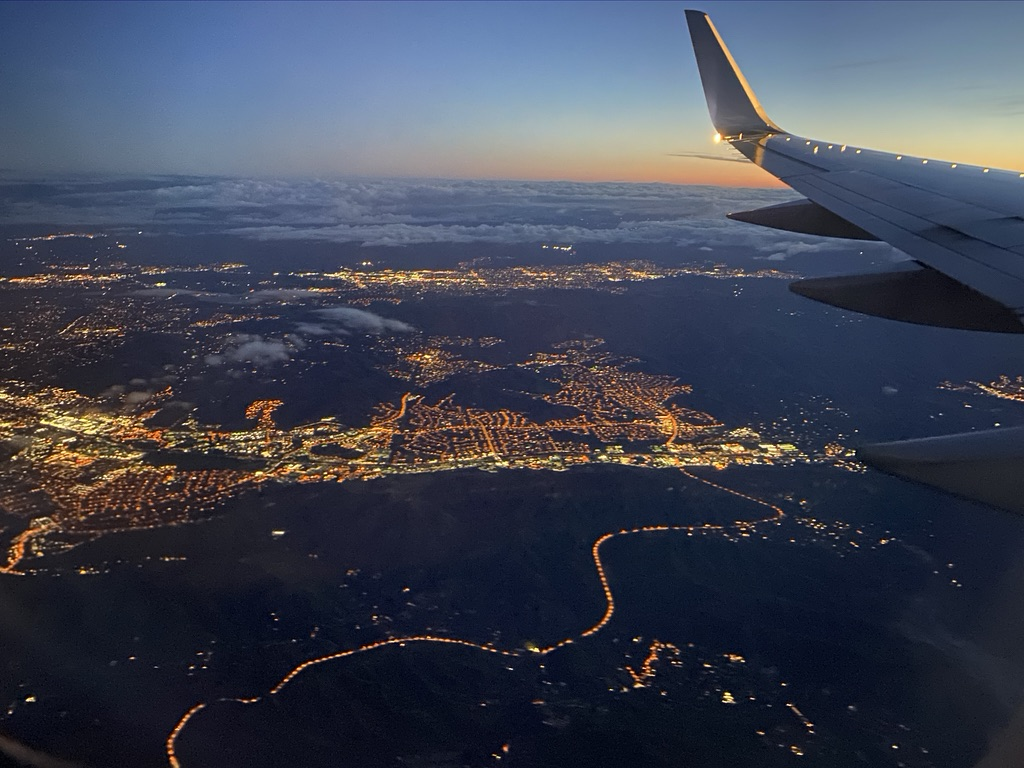 Stadt bei Nacht mit Flugzeugflügel
