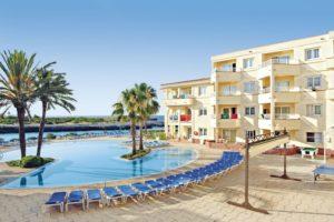 Swimmingpool mit Hotel und Palmen