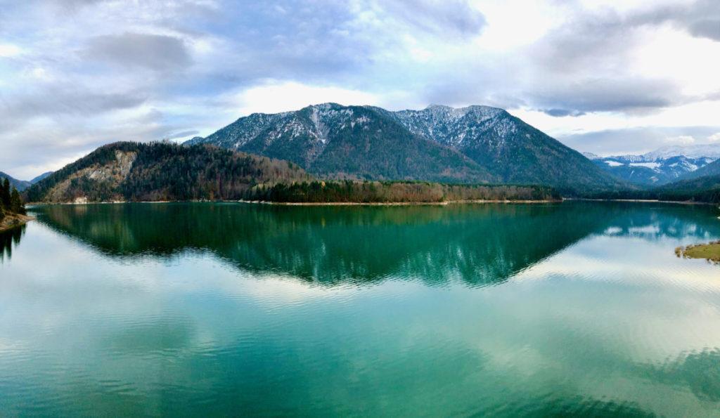 Grüner See vor Bergen und Wald